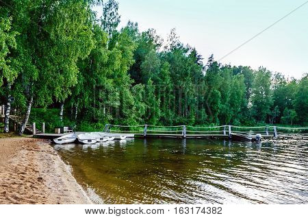 A quiet pier on the sandy shore of a forest lake with moored boats white on a forest background