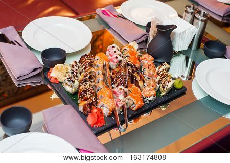 Different sushi on dark stone tray on served table in restaurant.Selective focus
