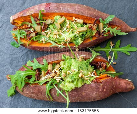 A baked sweet potato stuffed with arugula olives guacamole. Top view slate background. Vegan healthy lunch or dinner. Love for a healthy raw food concept.
