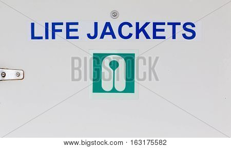 A Life Jackets Sign on a closet holding life jackets