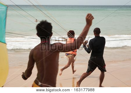 Girl is running on a beach with a parachute. Parasailing on a beach. Thailand.