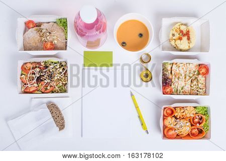 Healthy nutrition plan. Fresh daily meals delivery. Restaurant food for one vegetable meat and fruits in foil boxes detox water business card notebook and pencil on white background.