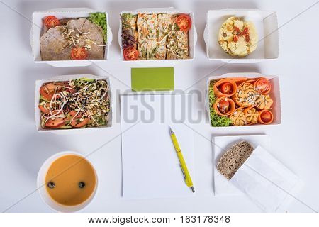 Healthy nutrition plan. Fresh daily meals delivery. Restaurant food for one vegetable meat and fruits in foil boxes business card notebook and pencil on white background.