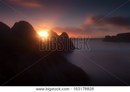Sun setting on the famous rockface at Three Cliffs Bay on the Gower peninsula in Swansea, South Wales