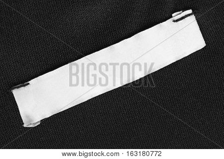 Blank white clothes label on black cloth