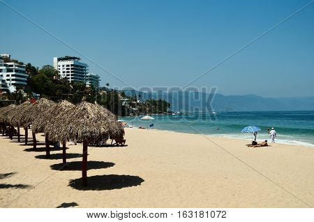 Beach,palapas and hotels from Playa Los Arcos in Puerto Vallarta, Mexico.