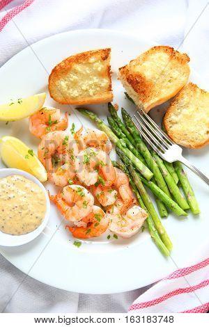 Shrimp dinner with asparagus garlic bread grainy-mustard sauce and lemon