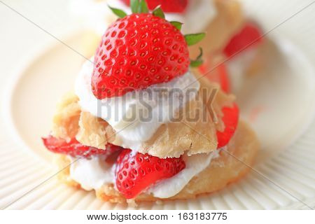Small, fresh, individual strawberry shortcakes on white plate closeup