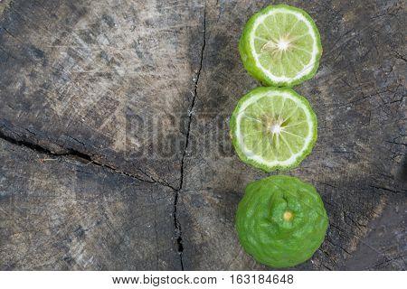 Bergamot (Kaffir lime) sliced on the old wood background