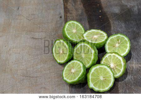 Bergamot (Kaffir lime) sliced on wood background