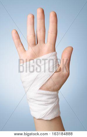 Injured painful hand with white gauze bandage