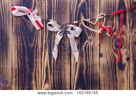 white bow and different ribbons hanging on a rope on a wooden background