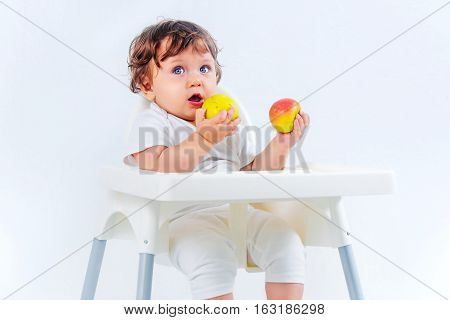 Happy baby boy sitting and eating apples fruits on gray studio background