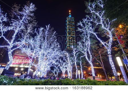 TAIPEI, TAIWAN - DECEMBER 23, 2016 - Christmas lights glow in front of the Taipei 101 building at night in the Xinyi Anhe district of Taiwan's capital city