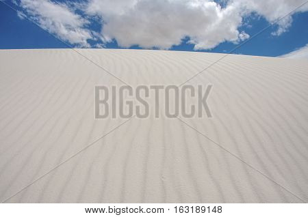 Photograph of the high white sand dunes of White Sands National Monument in New Mexico as they reach towards the sky.