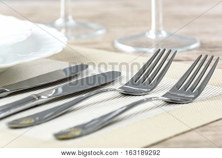 Elegant restaurant table setting with plates cutlery and stemware on a wooden table
