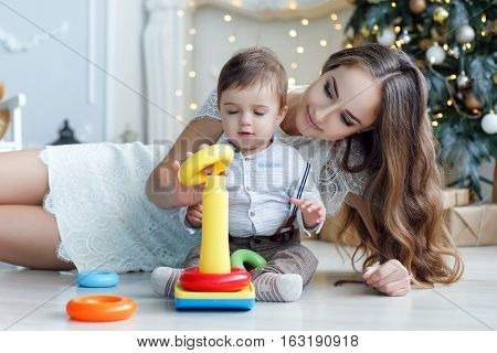 Young woman with long hair,dressed in a short white lace dress lies on white floor with sitting next to a young son,dressed in a white shirt and grey trousers,mother teaches son how to assemble a pyramid,the back is green decorated Christmas tree