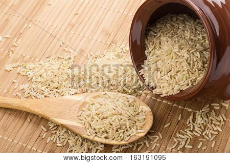 Overturned Pot Of Brown Rice And Wooden Spoon On Mat