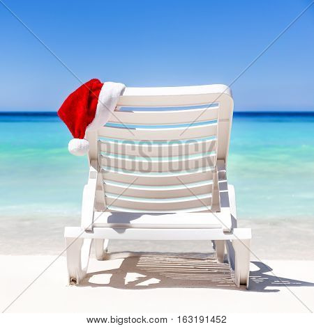 Santa Claus Hat On Sunbed Near Tropical Calm Beach With Turquoise Caribbean Sea Water And White Sand