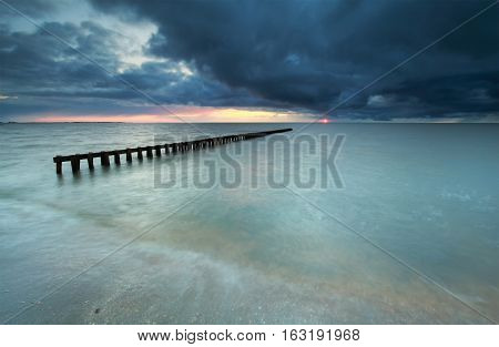 cloudy sunset on the sea coast with breakwater