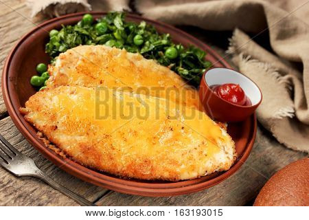 Chicken cheese schnitzel with green salad and spicy tomato sauce