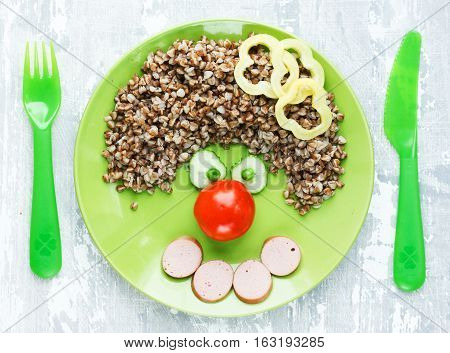 Creative idea for kids dinner or breakfast - buckwheat with sausage and vegetables in the shape of clown face. Fun food art for children meal top view