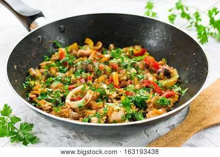 Seafood fried on pan with pepper egg and parsley. Stir fry from seafood mix and colorful vegetables