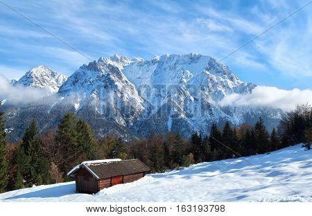 wooden trekker hut on snow in winter mountains