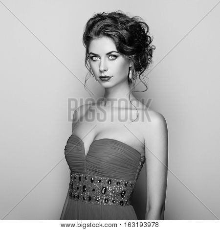 Fashion portrait of beautiful woman in elegant dress. Girl with elegant hairstyle and jewelry. Black and White