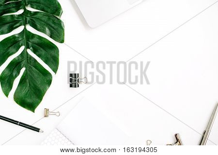 Home office workspace frame with laptop palm leaf and accessories. Flat lay top view