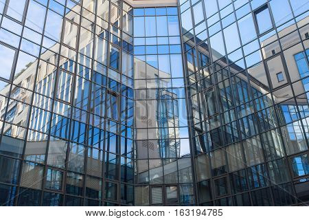 Reflection in a square glass-fronted façade. Architectural abstraction