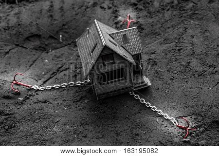 Model of the wooden house from a paper. The house stands on the ground. On the chain tied fishing hooks.