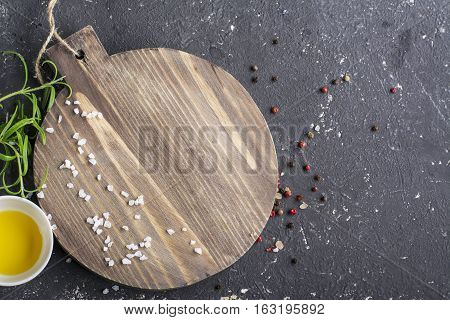 Rosemary, salt and pepper on wooden cutting board, copy space. Cooking food background. Top view