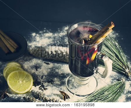 Glass of hot Mulled wine with sticks of cinnamon, anise and lemon on a blue wooden background. Winter, New Year, Christmas still life.