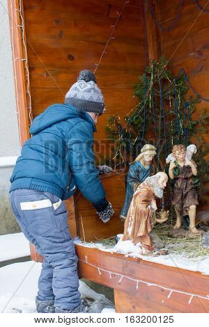 examines a little boy nativity scene figurines winter