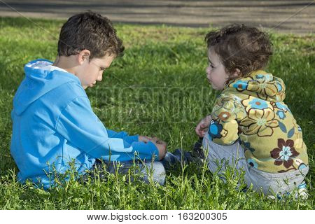 In the spring on the street on the grass boy sitting upset and his little girl comforts.