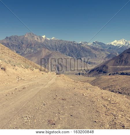 Desert road towards mountains. Annapurna circuit trek in Nepal.