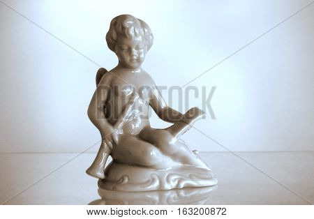 Serial porcelain figurine of an Angel playing a flute. Duo toned photo