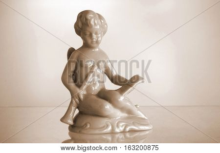 Serial porcelain figurine of an Angel playing a flute. Sepia toned photo