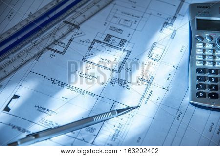 Architect working on blueprint. Architects workplace: architectural project, blueprints, ruler, calculator, laptop and divider compass.  Architect engineering tools