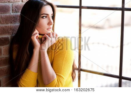 Portrait of brunette beautiful girl 20-25 year old wearing yellow knitted sweater holding the collar looking at window. Winter season.
