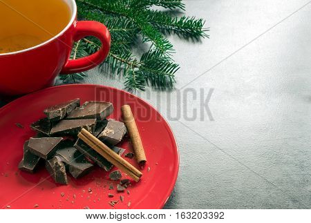 Green herbal tea and dark chocolate in a red ceramic bowl. Concept - hot drinks.