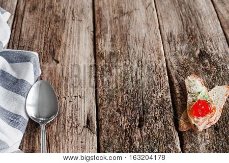 Canape with red caviar and spoon on wood void. Empty rustic table with cutlery and toast, free space for meal advertisement. Russian cuisine concept