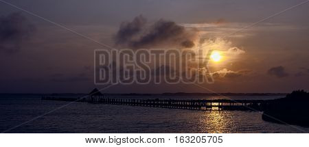 Panorama of an evening sunset over a bay. There is a silhouette of a wooden pier in the foreground. The location is Northside park in Ocean City Maryland.