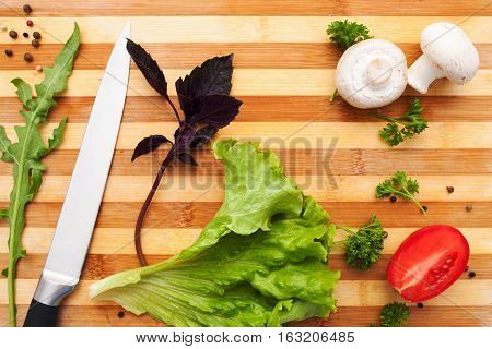 Cutting board with knife and vegetables flat lay. Top view on wooden kitchen workplace with fresh natural ingredients for cooking. Vegetarian cuisine, hobby, food preparation concept