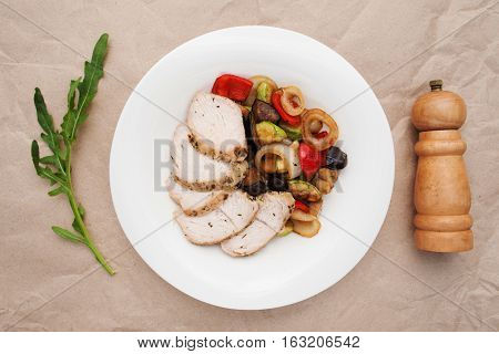 Vegetable ragout with chicken meat flat lay. Top view on beige table with hot dish of stewed vegetables ant poultry, with arugula and pepperbox. Healthy food, restaurant menu, concept