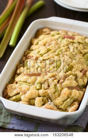 Freshly baked rhubarb crumble cake in baking dish photographed with natural light (Selective Focus Focus one third into the cake)