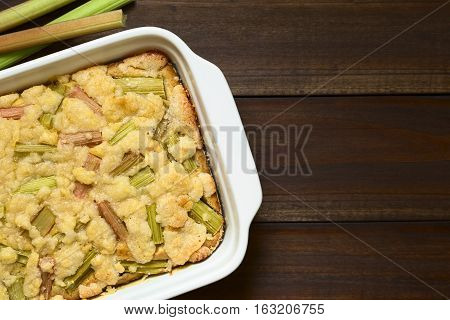 Freshly baked rhubarb crumble cake in baking dish photographed overhead on dark wood with natural light (Selective Focus Focus on the top of the cake)