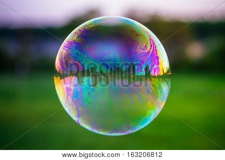Reflection of the colorful sunset sky in the soap bubble