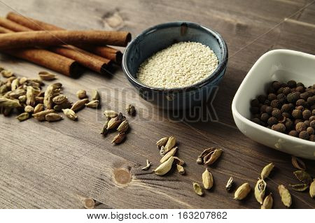 Mixed spice close-up. Cardamom cinnamon anise allspice sesame seeds in bowls on wooden table.